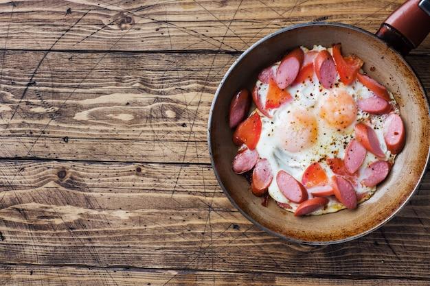 Pan met gebakken eieren worstjes en tomaten op de tafel.