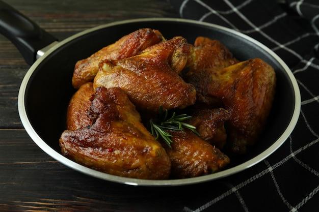 Pan met gebakken kippenvleugels en keukendoek op houten achtergrond