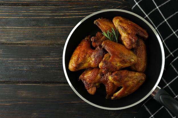 Pan met gebakken kippenvleugels en keukenhanddoek op houten