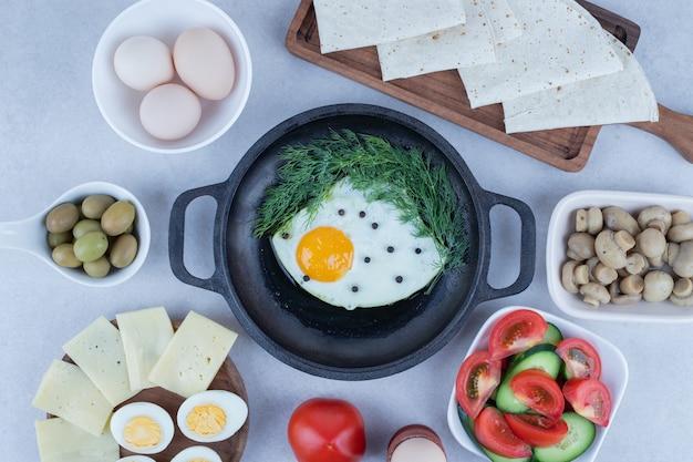 Pan met omelet en gekookte eieren, kaas, tomaat, champignons op wit.