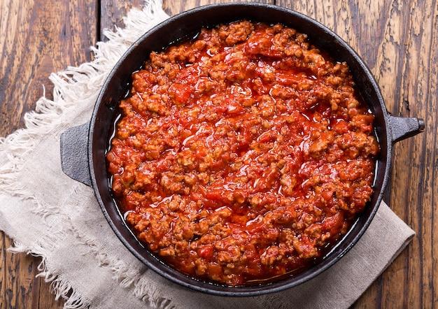 Pan met saus bolognese op houten tafel, bovenaanzicht
