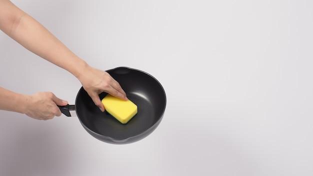 Pan schoonmaak man hand op witte achtergrond schoonmaken van de anti-aanbak pan met handige afwas spons