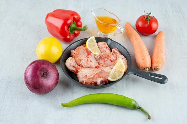 Pan van gekruide kip, olie en groenten op stenen oppervlak.