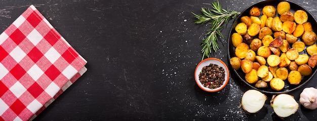 Pan van geroosterde aardappelen met rozemarijn op donkere tafel