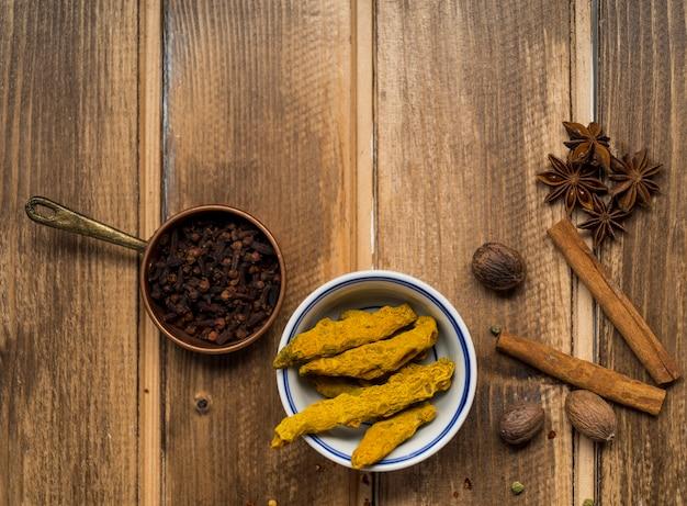 Pan van kruidnagels dichtbij aromatische kruiden