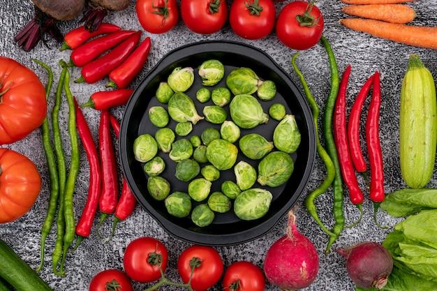 Pan vol spruitjes omgeven door kleurrijke groenten op een poederachtige