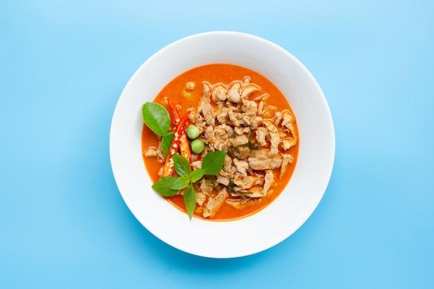 Panaeng curry met varkensvlees in witte kom op blauwe achtergrond. kopieer ruimte