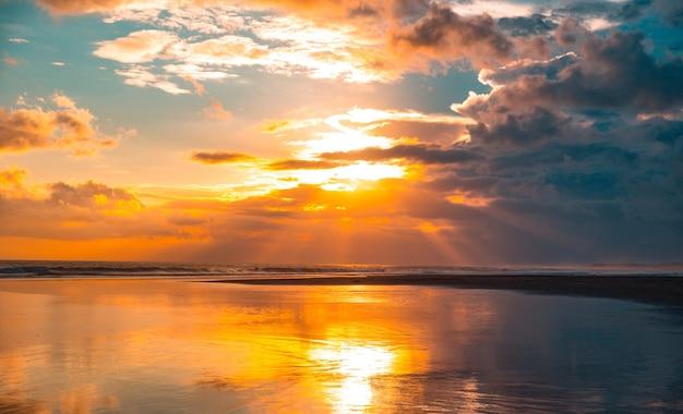 Panarama van de prachtige zonsondergang op de oceaan met bewolkte hemel
