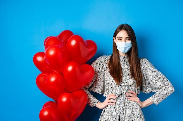Pandemie en valentijnsdag. vrolijk lachend meisje met medisch masker, staande in de buurt van romantische hartballonnen en kijkend naar de camera, gekleed in jurk, blauwe achtergrond.