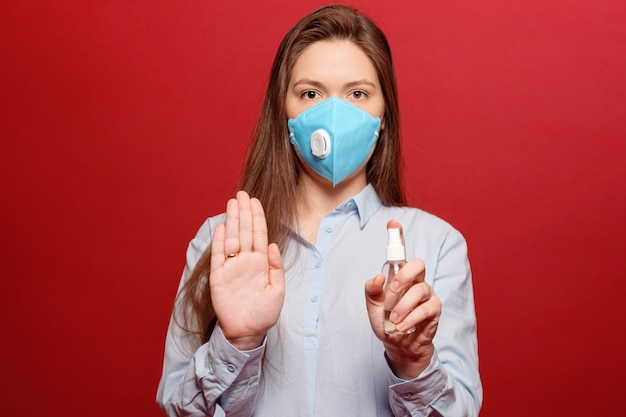 Pandemie van het coronavirus, close-upportret van jonge vrouw op rode achtergrond in beschermend medisch masker bespuit antiseptisch