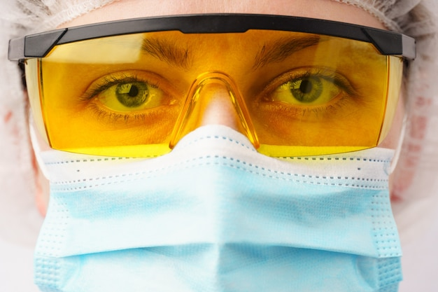Pandemisch coronavirus covid-19 de dokter draagt een chirurgisch masker en een veiligheidsbril.