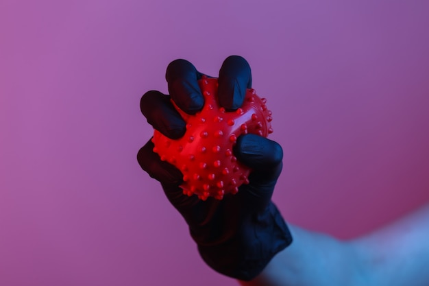 Pandemisch covid-19-thema. hand in beschermende handschoenen houdt een virusstammodel vast. rood blauw gradiënt neonlicht