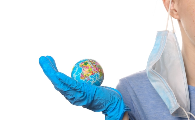 Pandemisch covid-19-thema overwinnen. vrouw in beschermende handschoenen, medisch gezichtsmasker houdt globe model geïsoleerd op wit.