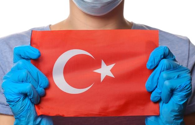 Pandemisch covid-19-thema. vrouw in beschermende handschoenen, medisch gezichtsmasker houdt de vlag van turkije geïsoleerd op wit.