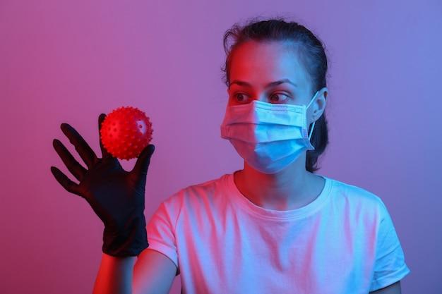 Pandemisch covid-19-thema. vrouw in beschermende handschoenen, medisch gezichtsmasker houdt een virusstammodel vast. rood blauw gradiënt neonlicht