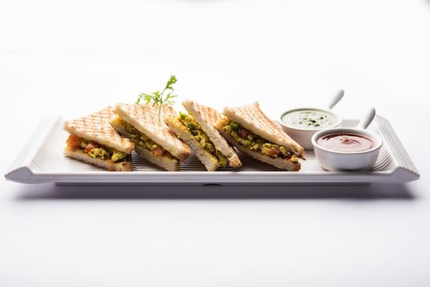Paneer bhurji sandwich is een smakelijk gerecht op basis van paneer gemaakt met kwark. geserveerd met verse tomatenketchup en groene muntchutney. selectieve focus