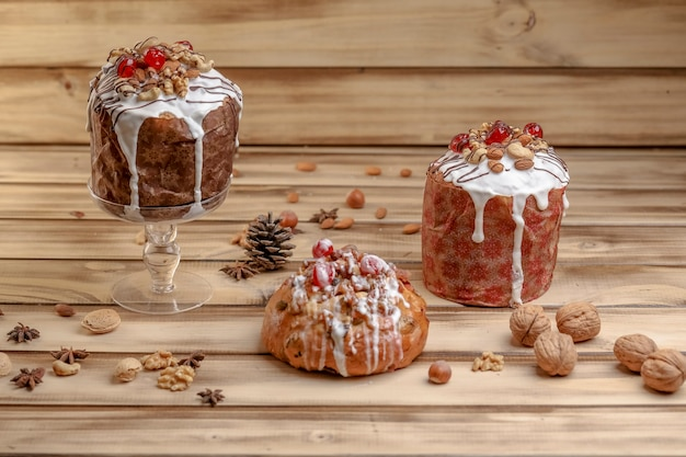 Panettone met fruit en glazuur, versierd voor kerstmis op houten achtergrond