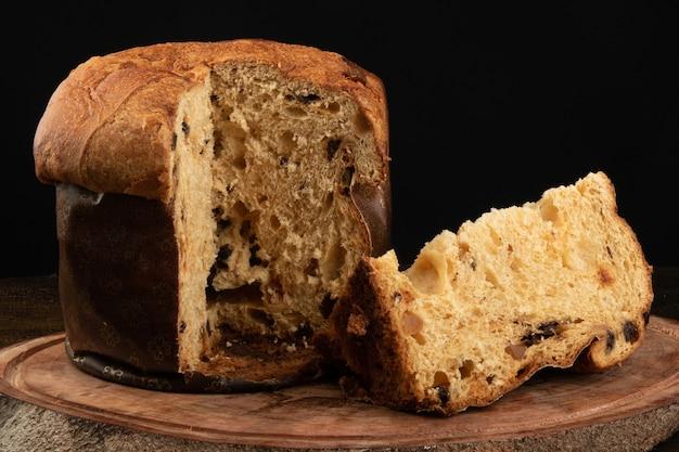 Panettone met gesneden traditioneel stuk van het kerstmisvoedsel met zwarte achtergrond.