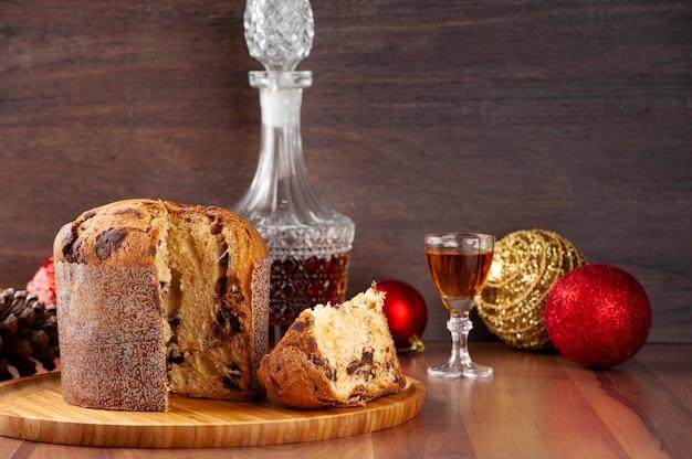 Panettone op een houten dienblad, glas sterke drank en kerstversiering.