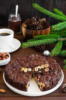Panforte. traditioneel italiaans kerstdessert met noten en gedroogd fruit op een witte plaat op een donkere houten achtergrond. verticaal, kopieer ruimte.