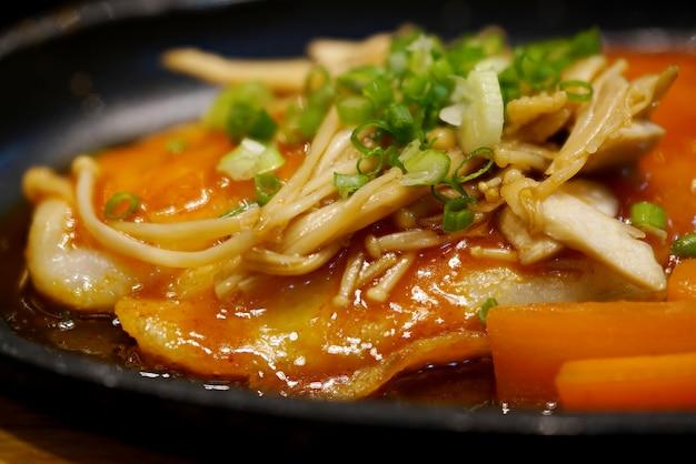 Pangasius vis steak kruiden met chili saus, champignons en fruit op zwarte plaat, macro focus.