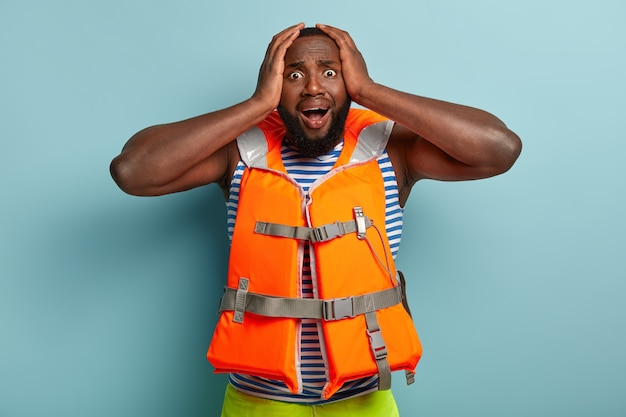 Paniking afro-amerikaanse man in reddingsvest, bang voor zomerski-activiteit
