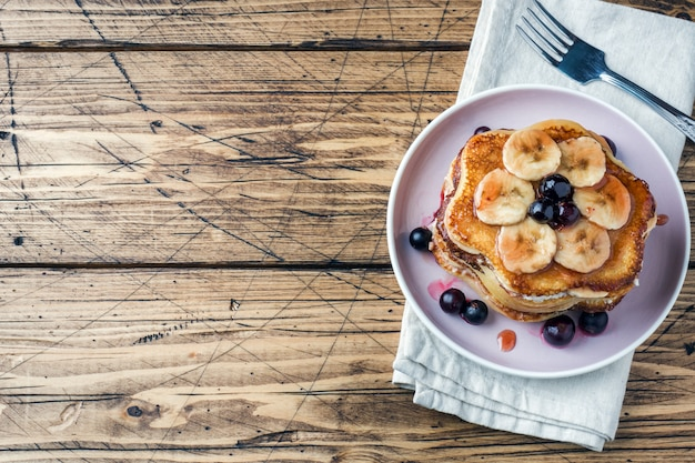 Pannekoekcake met bananen en bessenstroop, selectieve nadruk, donkere achtergrond. ruimte kopiëren
