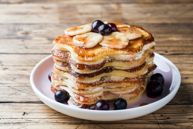 Pannekoekcake met bananen en bessenstroop, selectieve nadruk, donkere achtergrond.