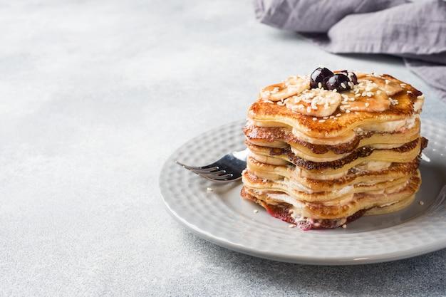 Pannekoekcake met bananen en bessenstroop, selectieve nadruk, grijze achtergrond.