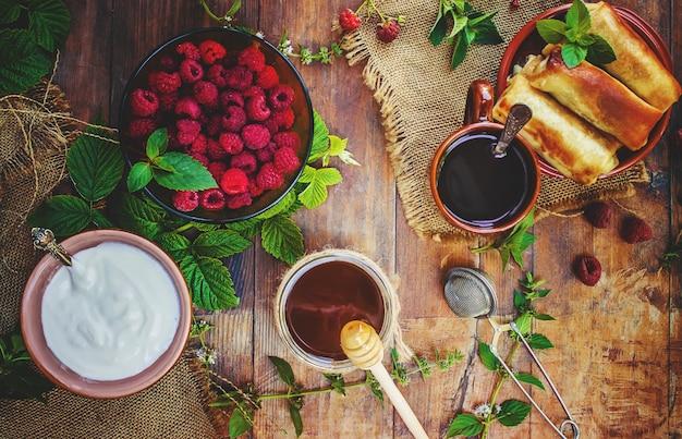 Pannekoeken en thee op een houten achtergrond. selectieve aandacht.