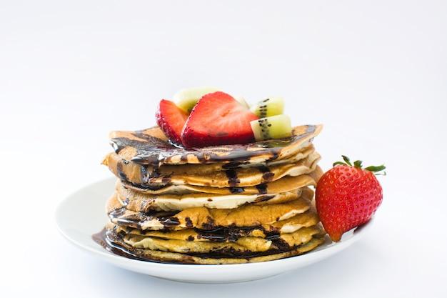 Pannekoeken met chocolade, aardbeien en kiwi op witte achtergrond