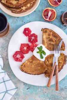 Pannekoeken met chocoladesaus met grapefruit en munt op een blauwe achtergrond
