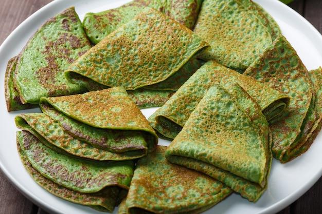 Pannekoeken met spinazie op witte plaat. ontbijt achtergrond