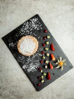 Pannenkoek gegarneerd met kokoschips en gesneden fruit