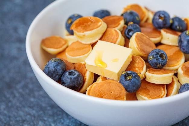 Pannenkoek granen met boter en bessen in een witte kom. ontbijt eten concept.