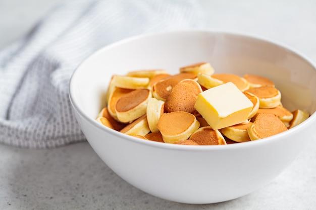 Pannenkoek granen met boter in een witte kom, kleine trend pannenkoeken. ontbijt eten concept.