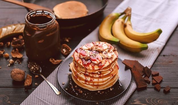 Pannenkoek met chocolade en notenpasta, walnoten en banaan op een zwart bord