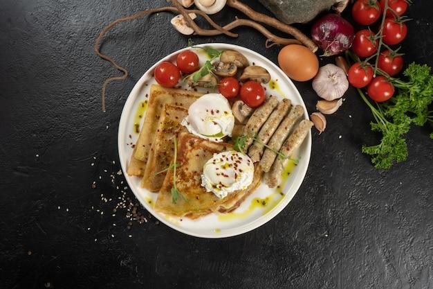 Pannenkoek met gegrilde kippenworstjes, champignons, kerstomaatjes en gepocheerd ei. een warm continentaal ontbijt