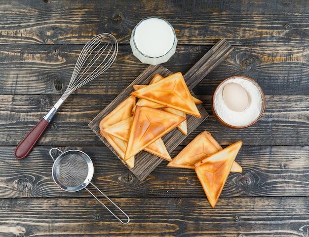 Pannenkoek op een houten bord met ingrediënten en gereedschappen
