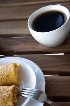 Pannenkoeken en zwarte koffie in een witte mok op een houten tafel, ontbijt