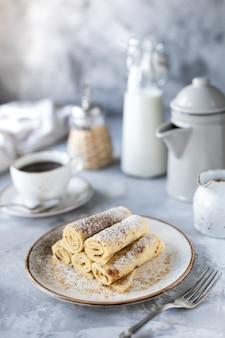 Pannenkoeken gestapeld op een bord op een witte tafel met een kopje koffie en een fles melk