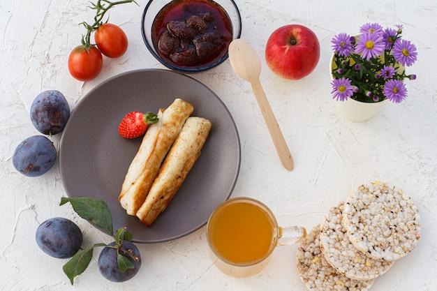 Pannenkoeken gevuld met kaas, jam in een kom, kopje thee, een plant en meer op witte bakstenen achtergrond