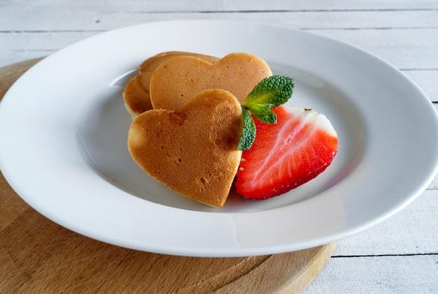 Pannenkoeken in de vorm van een hart met aardbeien.
