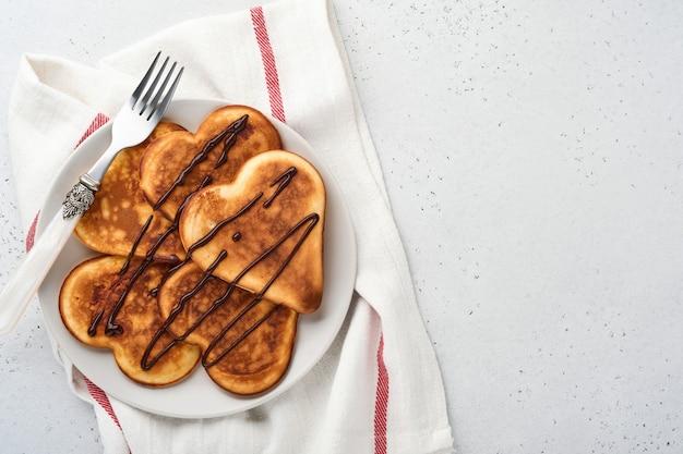 Pannenkoeken in de vorm van ontbijtharten met chocoladesaus in grijze keramische plaat, kopje koffie op grijze betonnen ondergrond. tabel instelling voor valentijnsdag ontbijt. bovenaanzicht kopie ruimte.
