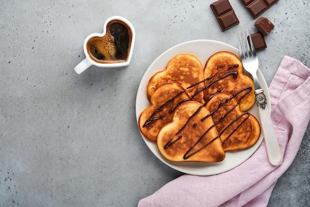 Pannenkoeken in de vorm van ontbijtharten met chocoladesaus in grijze keramische plaat, kopje koffie op grijze betonnen ondergrond. tafeldecoratie voor uw favoriete valentijnsdagontbijt. bovenaanzicht.