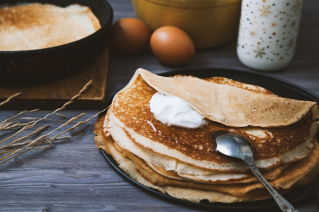 Pannenkoeken in een koekepan en ingrediënten voor hen op een houten tafel