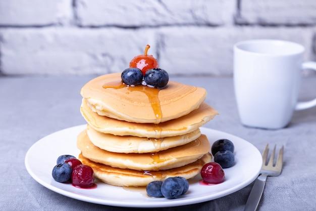 Pannenkoeken met ahornsiroop, bosbessen, kersen en een mini-appel. een kopje koffie op de achtergrond. traditionele amerikaanse pannenkoeken. detailopname.