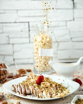 Pannenkoeken met banaan en aardbei, bedekt met melkchocolade en geraspte noten
