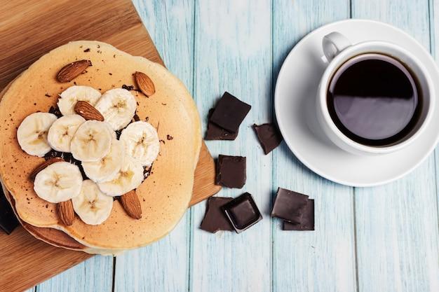 Pannenkoeken met banaan en noten op een houten bord, blauw licht oppervlak, bovenaanzicht