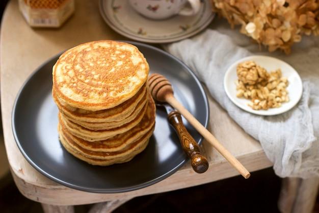Pannenkoeken met banaan, noten en honing, geserveerd met thee. rustieke stijl.